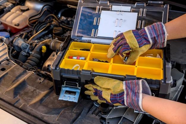 Ящик для инструментов с рукой на автомобильном двигателе крупным планом