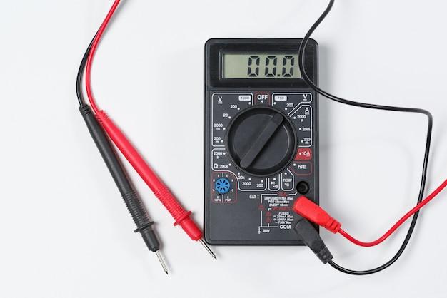 Инструмент для проверки электрических цепей. цифровой мультиметр на белой стене