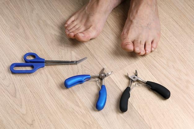 爪と男性の足を切るための道具は木の床にあります