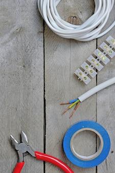 Инструмент для ремонта электриков на деревянном фоне. вид сверху. место для текста.