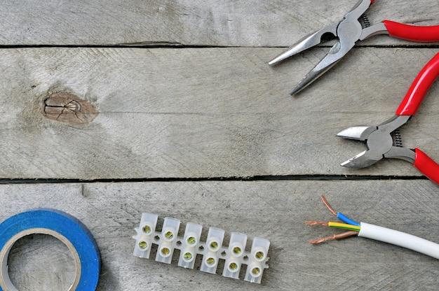 木製の背景の電気技師を修理するためのツール。上面図