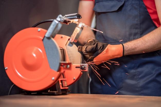 Станок для заточки инструмента. руки человека в рабочих защитных перчатках, шлифовальные детали на машине в мастерской, без лица