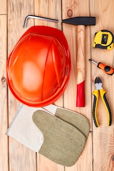 Tool kit on wooden backdrop. hard hat and work gloves. diy as a rule.