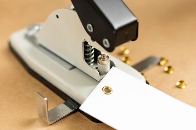 구멍 설치를 위한 도구 또는 수동 기계. 나무 테이블에 펀처 및 그로밋 설치