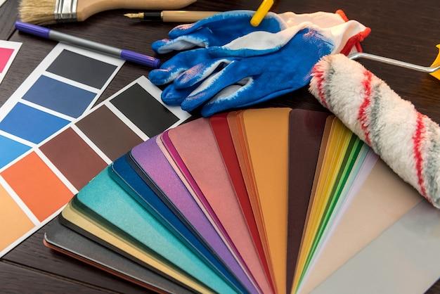 ツールペイントパレットとペイントブラシ、修理家用の青い手袋。宿題の背景