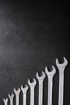 Tool wrenches in a row on a black background with free space.