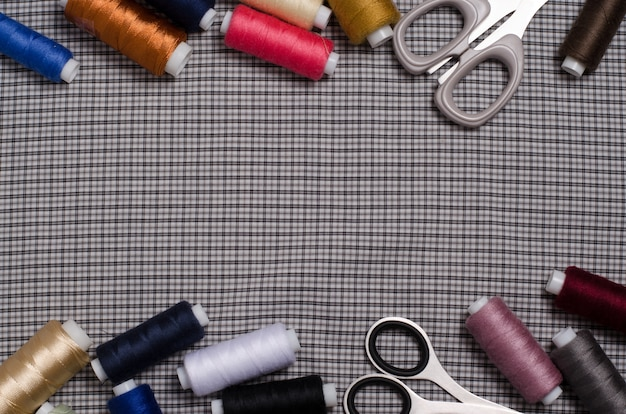Tools and accessories for sewing. sewing thread, scissors on gray