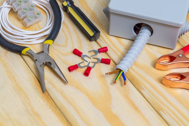 The tools and accessories used in electrical installation or repair on wooden workshop table