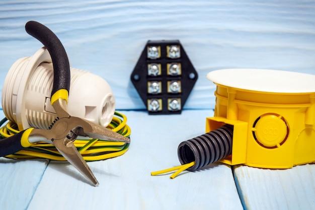 青い木の板の電気設備または修理に使用される工具および付属品