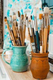 アーティストのためのツールと機器。パレットとブラシのクローズアップ。描画と創造性のプロセス。写真は青です。