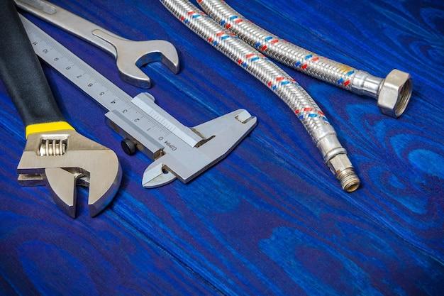 青い木製ボード上の配管工のためのツールとホース