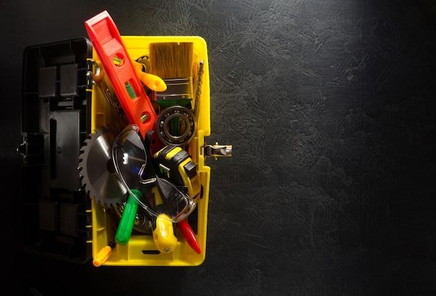 검은 벽에 도구 상자와 도구 및 악기