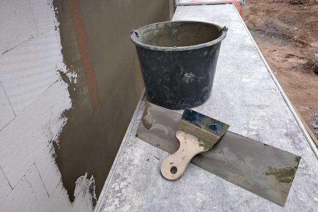 仕上げ塗装前に保護用接着剤で壁を覆うツールと材料
