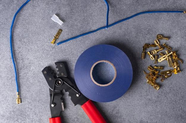 Инструменты и материалы для зачистки и опрессовки концов многожильных электрических проводов. вид сверху.