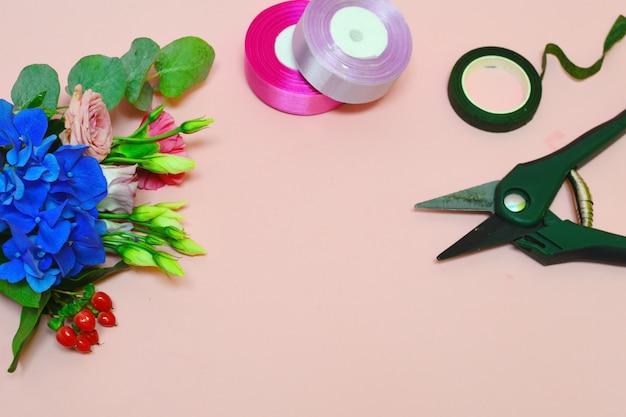 花屋の道具と材料。美しい楽しい作品。フラワーサロンのコンセプト。花の梱包材。美しいピンクの背景にバラの茂み