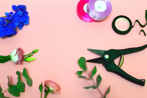 花屋の道具と材料。美しい楽しい作品。フラワーサロンのコンセプト。美しいピンクの背景にバラの茂み