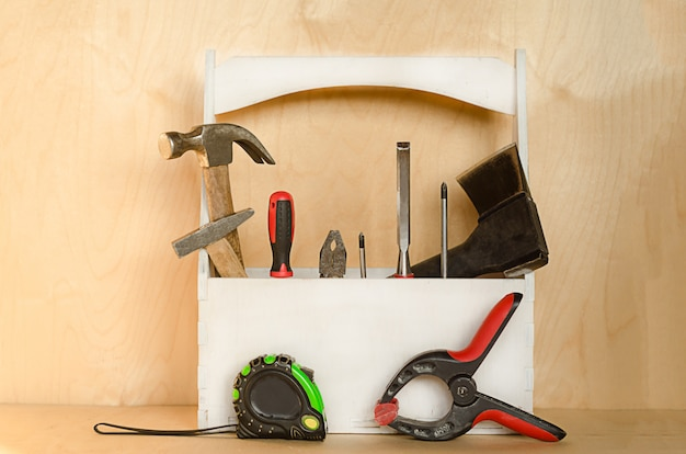 Tools for carpenter in box on wooden background