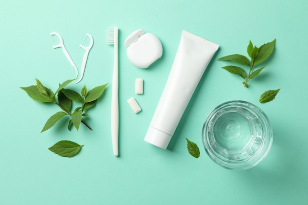 Tools for dental care on mint background, top view