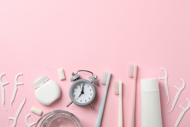 Tools for dental care on pink background, top view