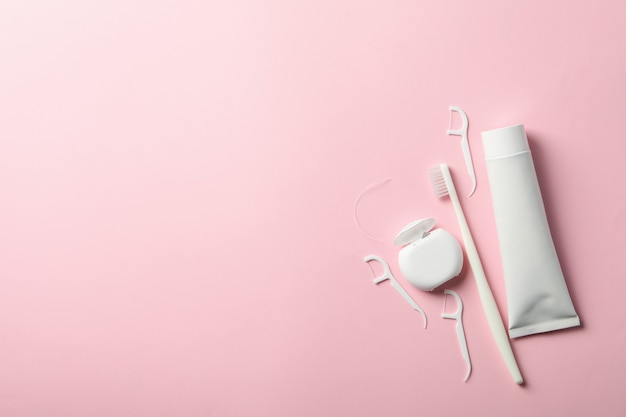 Tools for dental care on pink surface