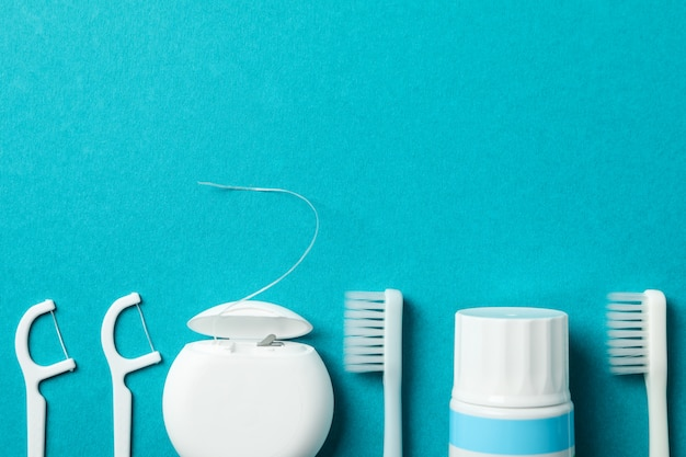 Tools for dental care on turquoise background, space for text
