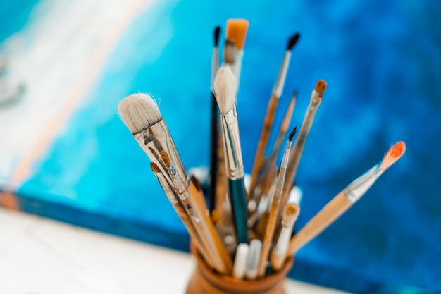 Tools and equipment for the artist. palette and brushes close-up. the process of drawing and creativity. the picture is in blue.