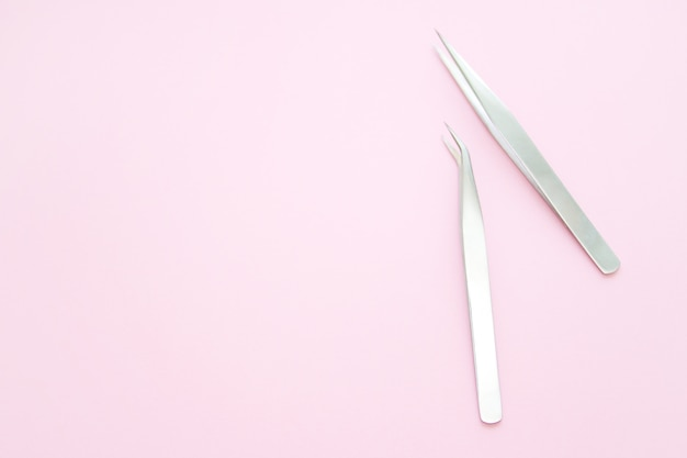 Tools for eyelash extension procedure. two tweezers on pink background.
