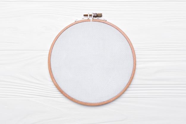 クロスステッチ用のツール。白い木製の背景に刺繡と帆布のフープ。