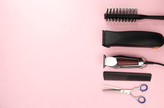 분홍색 배경에 머리카락을 자르고 스타일링하기 위한 도구