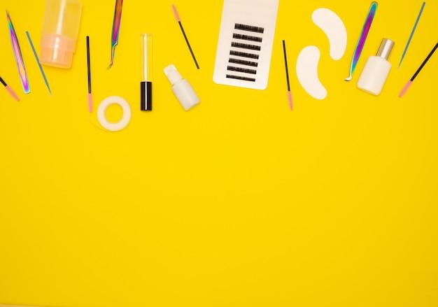 Инструменты для наращивания ресниц на желтом фоне
