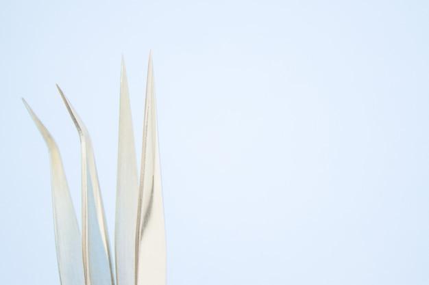 Инструменты для наращивания ресниц. два пинцета на синем фоне