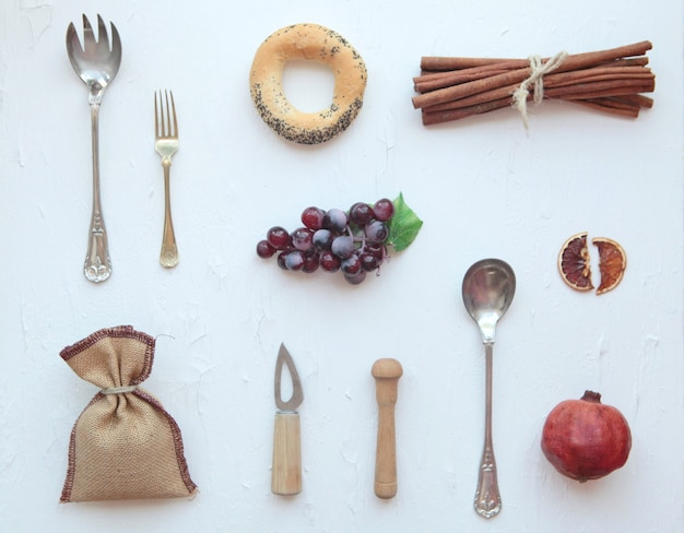 음식 사진 도구 - 칼, 숟가락, 큰 계피, 포도, 오렌지, 위쪽 전망. 흰색 배경에.
