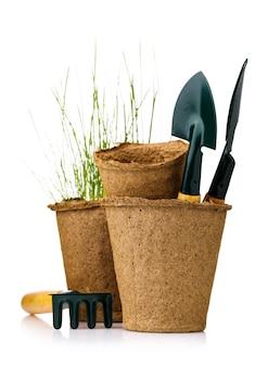 白い背景で隔離の苗とシャベルで泥炭ポットをガーデニングするためのツール