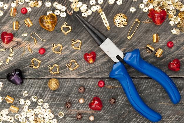 Инструменты для украшений ручной работы рядом с бусинами, плоскогубцами, стеклянными сердечками и аксессуарами для создания украшений ручной работы.