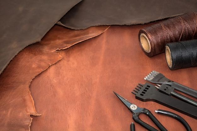 Инструменты для обработки кожи и кусочки коричневой кожи. производство кожгалантереи. вид сверху плоская планировка. пустое место для текста
