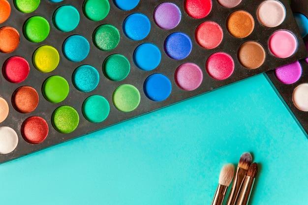 메이크업 및 화장품용 도구는 다양한 색조의 아이섀도우 팔레트와 최신 유행의 다채로운 파란색 파스텔 배경에 브러시를 만듭니다. 평면도와 그림 같은 평면도