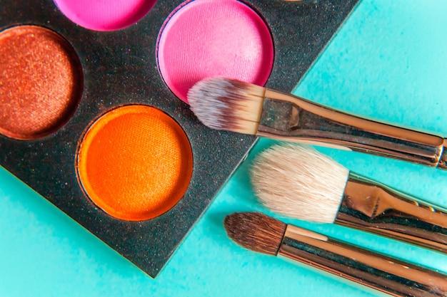 메이크업 및 화장품을위한 도구 아이섀도 팔레트의 다른 음영과 트렌디 한 다채로운 파스텔 배경에 브러시를 구성하십시오.