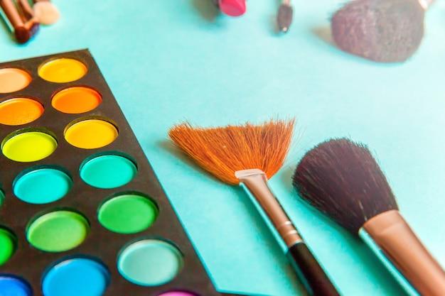 Инструменты для макияжа и косметики разных оттенков палитры теней и кисти для макияжа на модном красочном голубом пастельном столе. плоский вид сверху