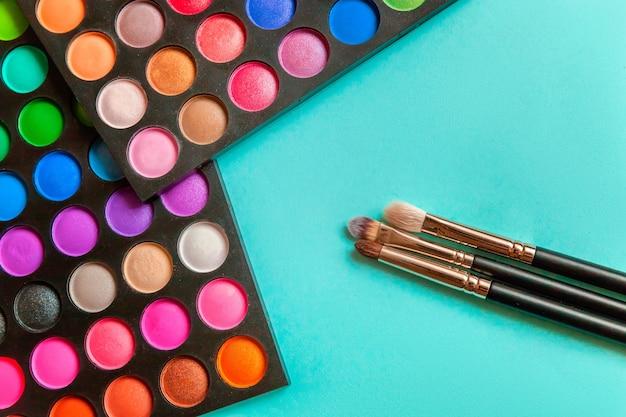 メイクや化粧品のアイシャドウパレットのツールは、青い背景のブラシを構成します