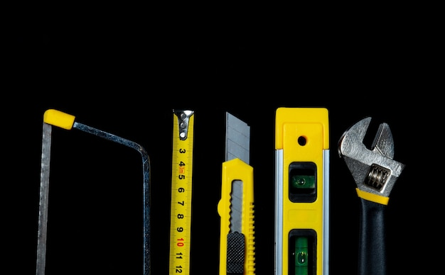 黒の背景にマスタービルダーのためのツール。建設ツールのクローズアップ。上面図