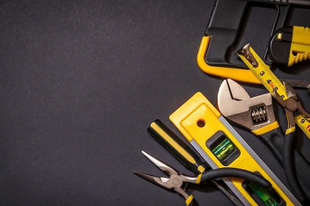 Инструменты для мастера-строителя на черном фоне с местом для рекламы
