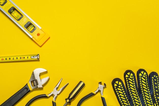 黄色の背景にマスタービルダーのためのツール