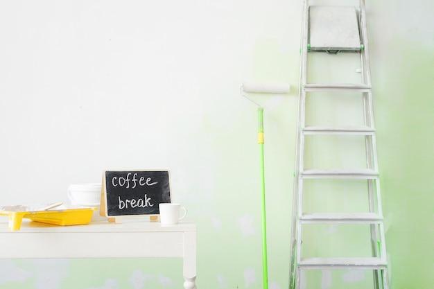 Инструменты для покраски стен и чашка кофе.