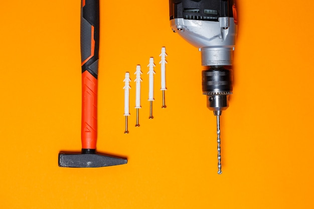 Инструменты для ремонта. молоток для гвоздей, дрель, дюбель в стене на оранжевом фоне. инструментарий для мастера