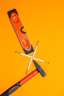 수리용 도구. 주황색 배경의 벽에 못, 수평, 다웰용 망치. 마법사용 툴킷