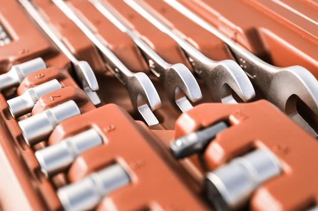 서비스 및 수리 도구는 갈색 상자, 금속 장비, 작업용 렌치에 클로즈업됩니다.