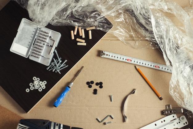 Инструменты для сборки мебели, мебельные детали, упаковочная пленка, шурупы на листе картона. сборка мебели вручную. концептуальная мастерская. плоская планировка, вид сверху