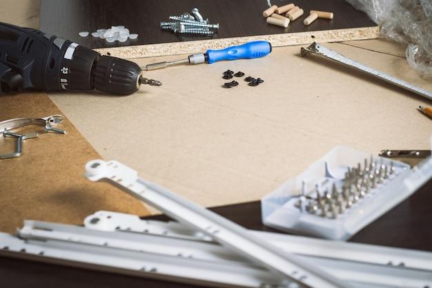 Инструменты для сборки мебели, мебельные детали, упаковочная пленка, шурупы на листе картона. сборка мебели вручную. концептуальная мастерская