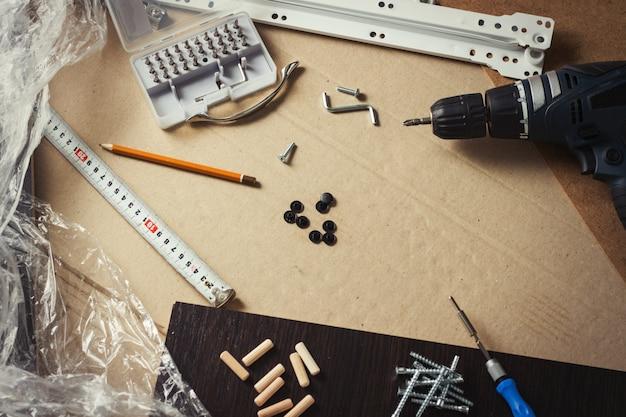 Инструменты для сборки мебели, мебельные детали, упаковочная пленка, шурупы на листе картона. концептуальная мастерская