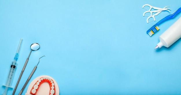 Инструменты для ухода и лечения зубов стоматологические инструменты и зубная щетка и зубная паста на синем